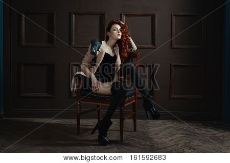 The red-haired girl posing on a chair her gaze beckons she flirts.