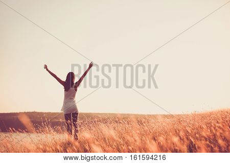 Free woman raising arms to golden sunset. Freedom and success concept. Girl relaxing and enjoying nature with copy space. Toned film effect