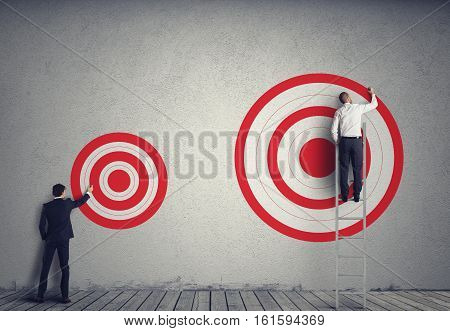 Businessman drawing a bigger target of his colleague. Achieve more important goals in work concept