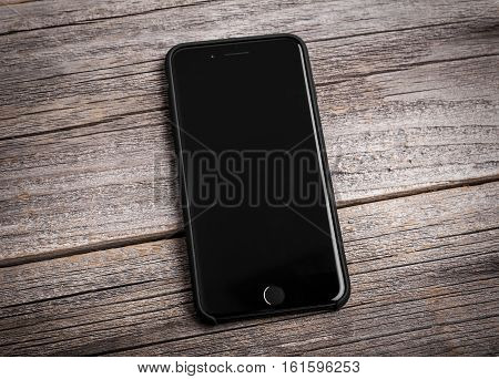 UZHGOROD, UKRAINE - DECEMBER 15, 2016: New black iPhone 7 Plus from the company Apple on a woden background in the silicone cover, studio photo, on December 15, 2016 in Uzhgorod, Ukraine.
