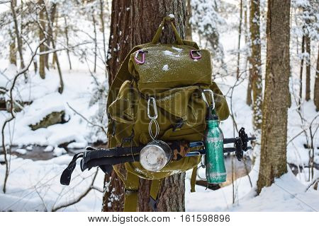 Hiker's backpack hanging from a tree on a winter's day.