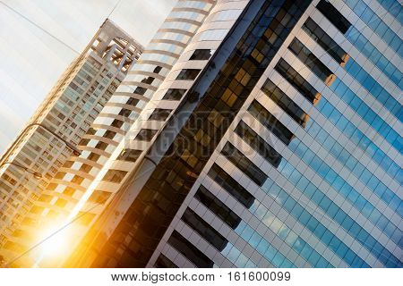 High Glass Modern Building With Blue Sky And Cloud At Sunset For Abstract Background. Facades Textur