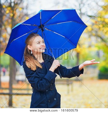 Young Woman With Blue Umbrella In The Luxembourg Garden Of Paris On A Fall Or Spring Rainy Day
