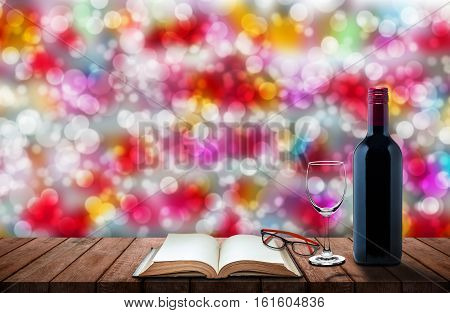 bottle of wine with galss of wine blank book and eyes glasses on wooden table with bokeh background