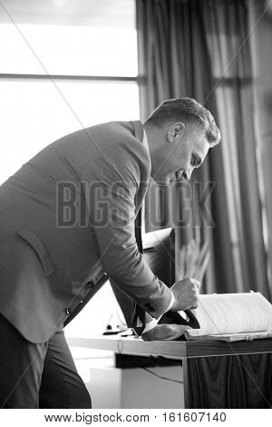 Side view of confident mature businessman reading book at desk in office