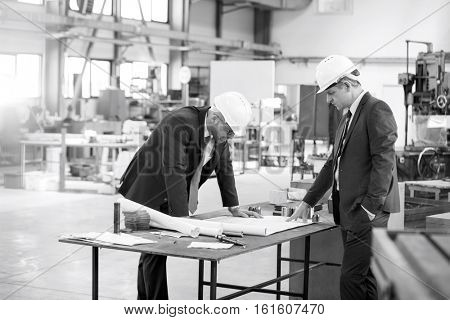 Businessmen examining blueprint at workbench in metal industry