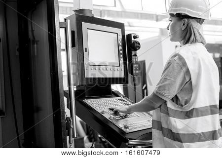 Side view of female worker operating machinery at control panel in factory