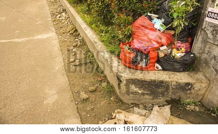 plastic trash bag in sidewalk using red bags photo taken in depok jakarta indonesia java