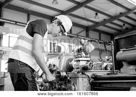 Side view of mid adult male worker operating machinery in metal industry