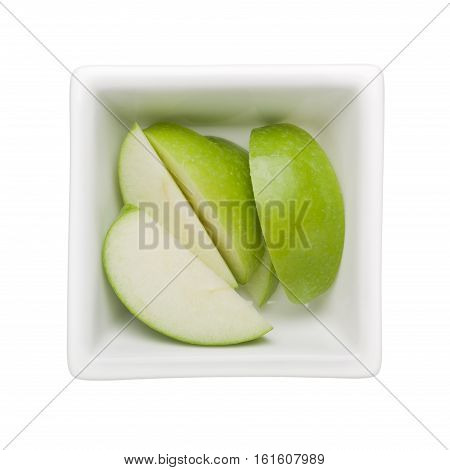 Slices of green apple in a square bowl isolated on white background