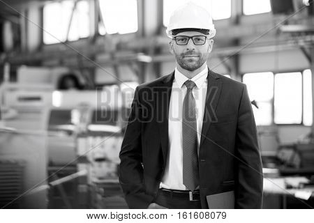 Portrait of confident mid adult businessman wearing hardhat in metal industry