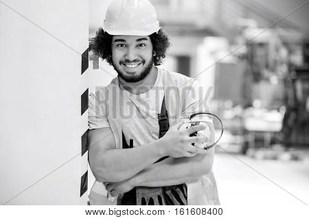 Portrait of confident male worker in protective clothing holding ear protectors at factory