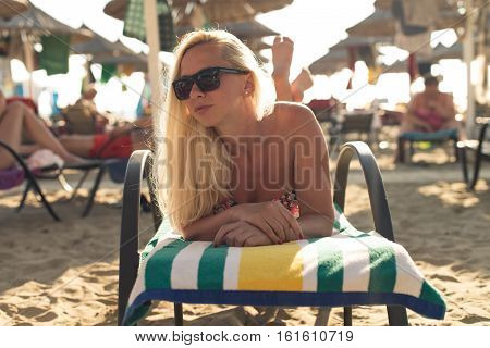 Beautiful Young Blonde Woman Sunbathe On The Beach