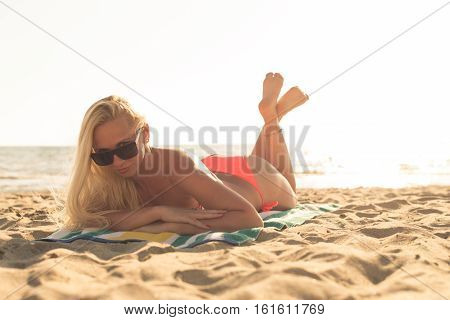 Attractive Girl In Sunglasses Lies On Warm Sand