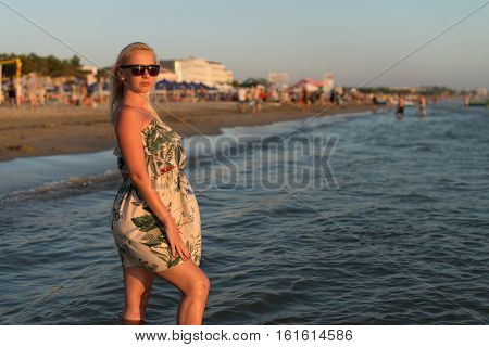 Beautiful Woman In Dress Walking On The Beach