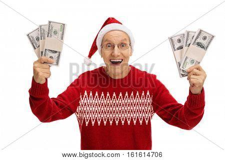 Overjoyed senior with a Christmas hat holding bundles of money isolated on white background