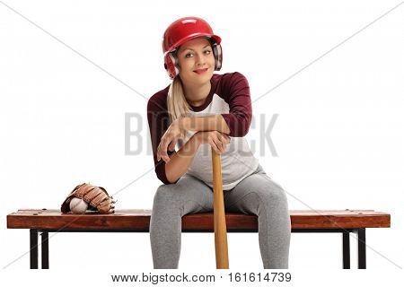 Woman with a helmet and a baseball bat sitting on a wooden bench isolated on white background