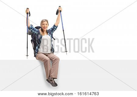Overjoyed female hiker sitting on a panel isolated on white background
