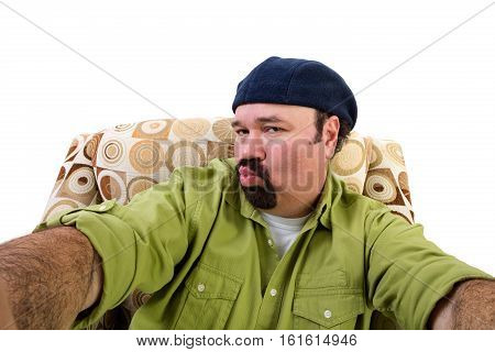Man In Armchair Blowing Kiss And Taking Selfie