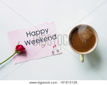Coffee mug with red rose flowers and happy weekend wording on notes of top view
