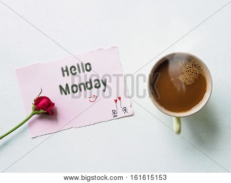Hello Monday message write by hand and coffee mug with red rose flowers on white table