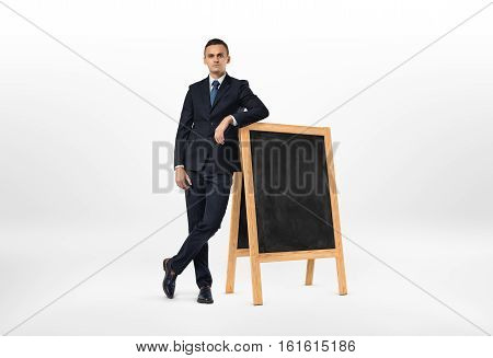 Businessman with a serious face leaning on the small blackboard isolated on the white background. Lack of ideas. Business development. Business learning.