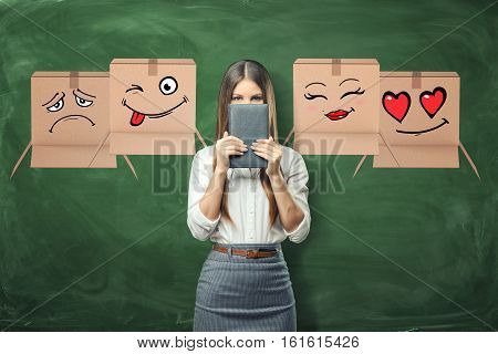 Young businesswoman surrounded by flying cardboard boxes with different faces drown on them on green chalkboard background. Daily planning. Time-management. Work is done. Emotions and feelings.