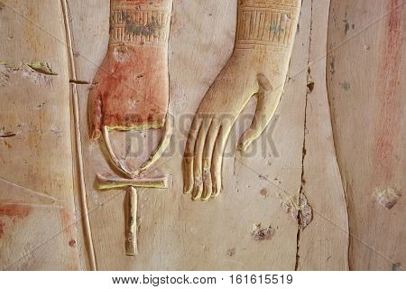 Ankh, an ancient Egyptian symbol of eternal life, in hand of a god, on the wall of the temple near Luxor (Thebes), Egypt