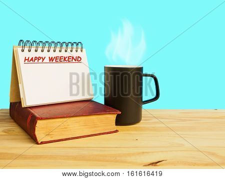 Mug of coffee on wooden floor with old book and happy weekend note of blue background happy weekend concept.