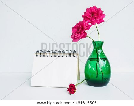 Blank calendar with rose flower in vase on white desk with copy space