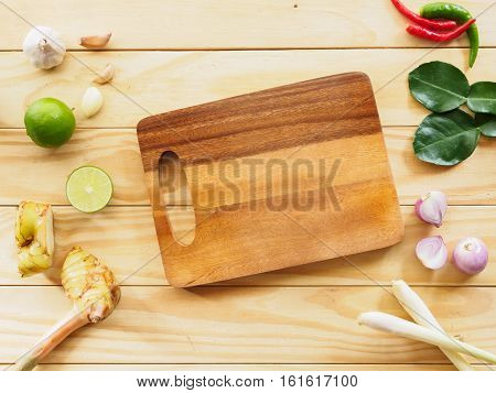 Flat lay chopping block and various vegetable of ingredient cooking food on wooden background with copy space