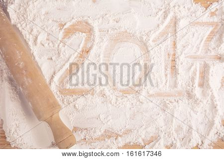 Happy new 2017 year on flour on wooden background. New year concept.