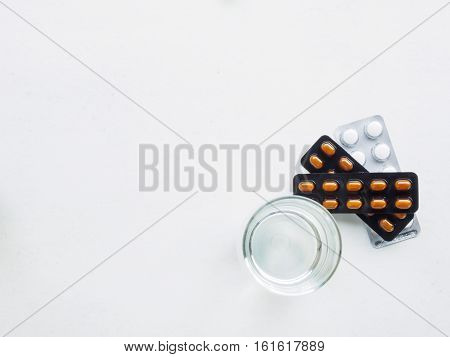 Top view of water glass and medicine on white background for treat fever with copy space