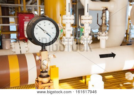 pressure gaugepressure gauge measuring gas pressure. Pipes and valves at oil and gas industrial plant.
