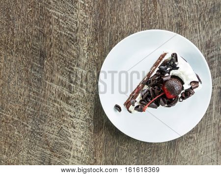 Chocolate cake with white white cream and cheery on plate of rustic wooden Top view and copy space