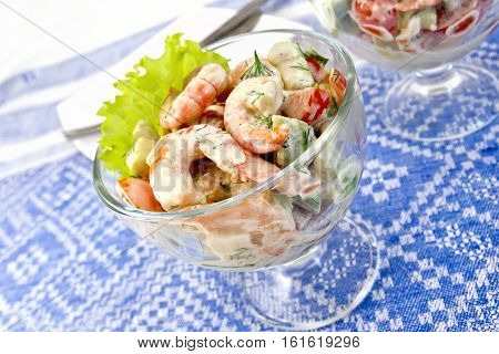 Salad with shrimp, avocado, tomato and mayonnaise, green salad in a glass goblet on a background of blue linen tablecloth