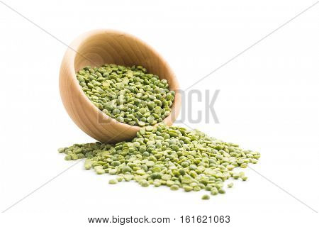 Green split peas in wooden bowl isolated on white background.