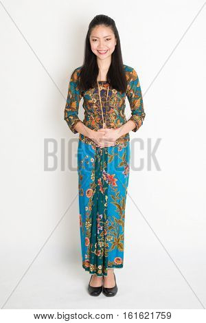 Portrait of young southeast Asian girl in traditional Malay batik kebaya dress smiling, full body standing on plain background.