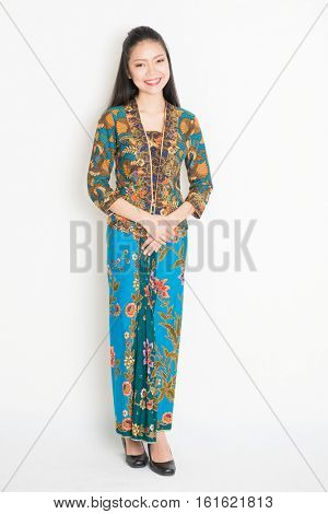Portrait of young southeast Asian woman in traditional Malay batik kebaya dress smiling, full body standing on plain background.