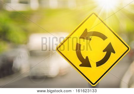 Roundabout Warning Sign On Blur Traffic Road With Colorful Bokeh Light Abstract Background.