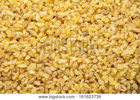 Bulgur grains, cracked wheat as a background. Macro shot of bulgur / bulghur