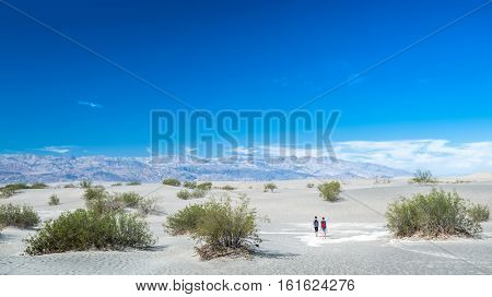 Couple of hikers in the sandy desert of the Death Valley National Park, USA