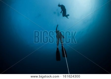 Free diver ascending along the rope in the depth.