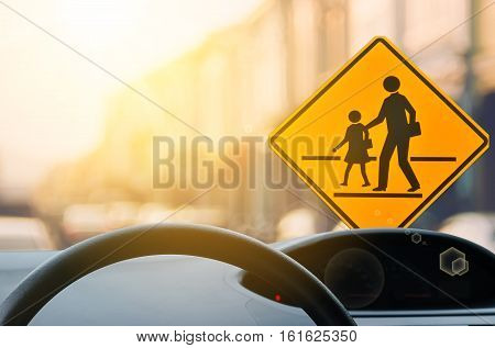 School Zone Warning Sign And Inside Car View ,steering Wheel On Blur Traffic Road With Colorful Boke