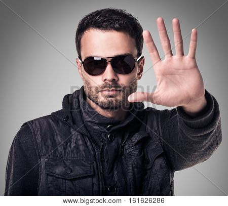 Handsome young man in sunglasses making stop sign over gray background