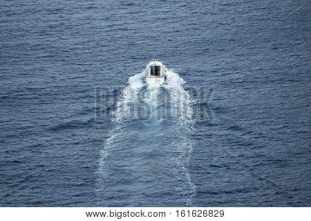 Long shot of small boat navigating, calm sea