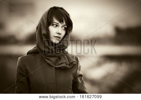 Sad young woman in classic coat walking on city street. Stylish fashion model outdoor