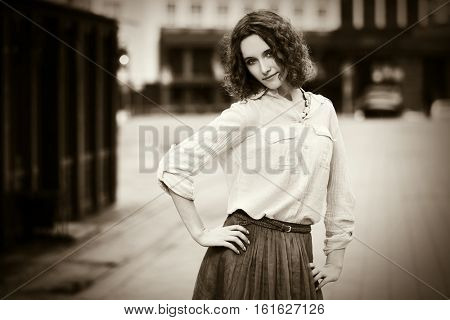 Happy young woman with curly hairs walking on city street. Stylish fashion model outdoor