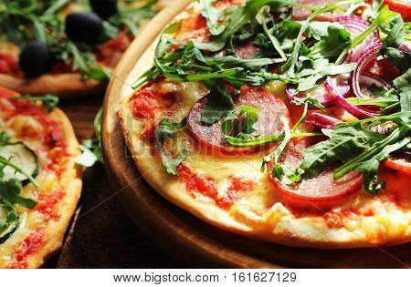 Different variations  of pizza.Pizza with sausage, zucchini, olives, cheese,  rucola.