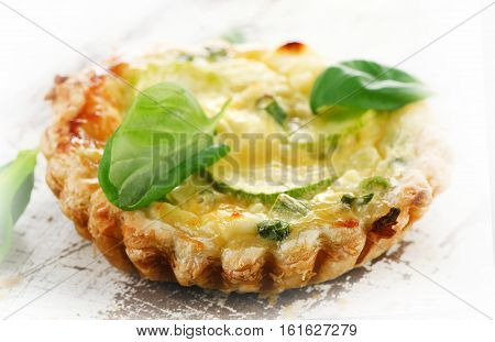 Tart With Cheese On A White Wooden Table.